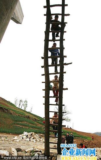 大桥和岸边连接不上,大伙就用木头做了梯子,先是从河滩的梯子爬上桥
