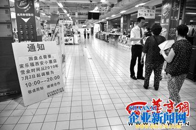 昨晚8时整,家乐福小寨店超市入口处,一员工向顾客告知营业时间